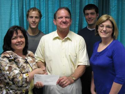 Family handing over donation check