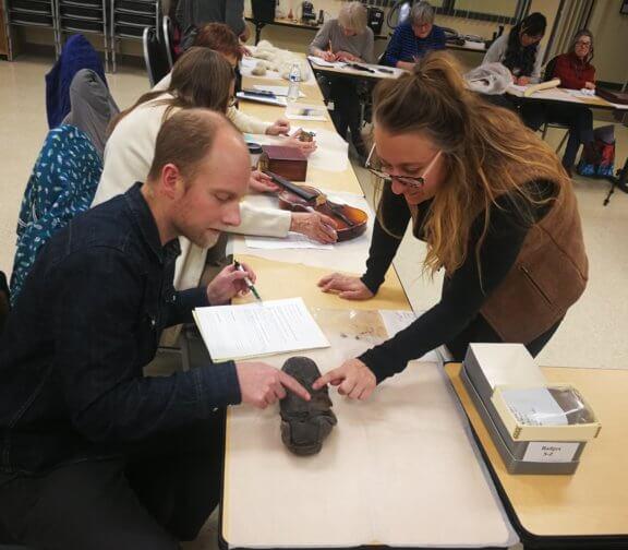 man and woman examining museum artifact